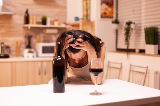 Femme pensant au suicide après avoir bu une bouteille de vin à cause d'un problème de vie et de dépression. maladie de la personne malheureuse et anxiété se sentant épuisée par des problèmes d'alcoolisme.