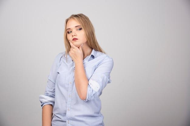 Femme pensant profondément à quelque chose sur une surface grise
