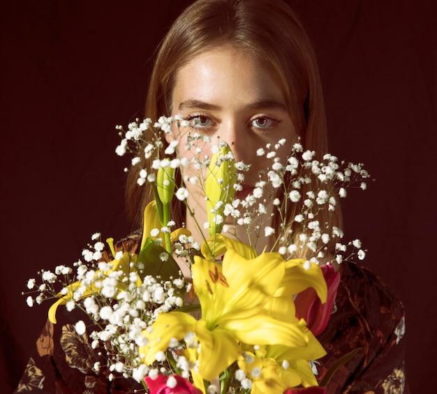 Femme pensif avec bouquet de fleurs