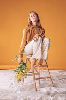 Femme pensif, sur, échelle, à, bouquet fleurs