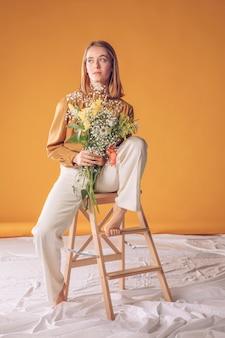Femme pensive, assis sur une échelle avec bouquet de fleurs