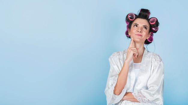 Femme pensive en bigoudis et peignoir blanc