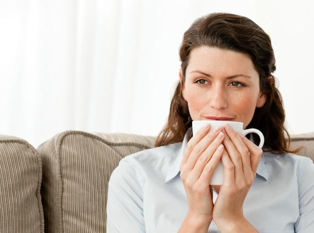 Femme pensive, boire du café dans le salon