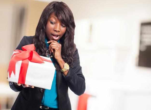 Femme pensive avec un cadeau blanc