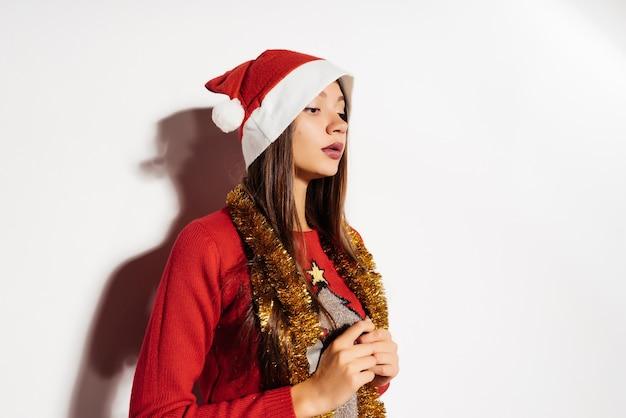 Femme pensive dans un chapeau de noël sur fond gris