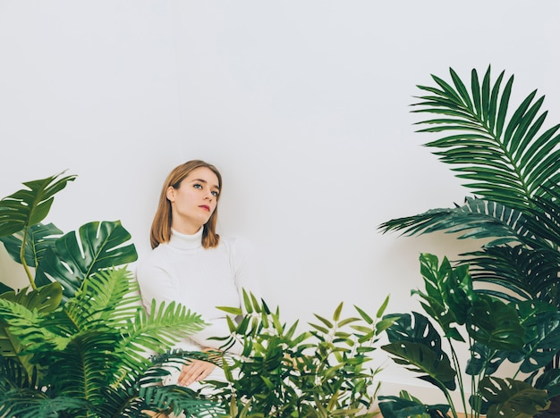 Femme pensive, debout près de plantes vertes