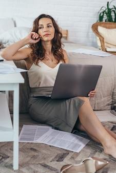Femme pensive est assise sur le sol avec un ordinateur portable à la maison.