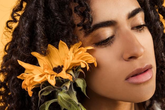 Femme pensive ethnique sensuelle avec fleur