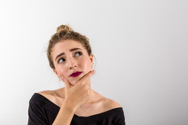 Femme pensive sur fond blanc. regarder avec un espace pour le texte