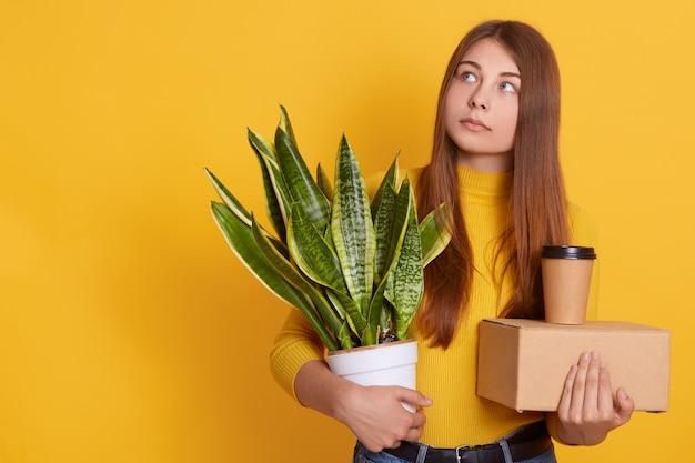 Une femme pensive habille des vêtements décontractés en tenant son personnel et son pot de fleurs dans les mains, en regardant de côté, pense à son licenciement, étant triste, l'air réfléchi, debout isolée sur un mur jaune.