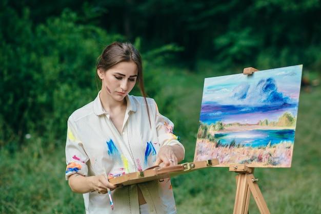 Femme pensive regardant une boîte de peintures
