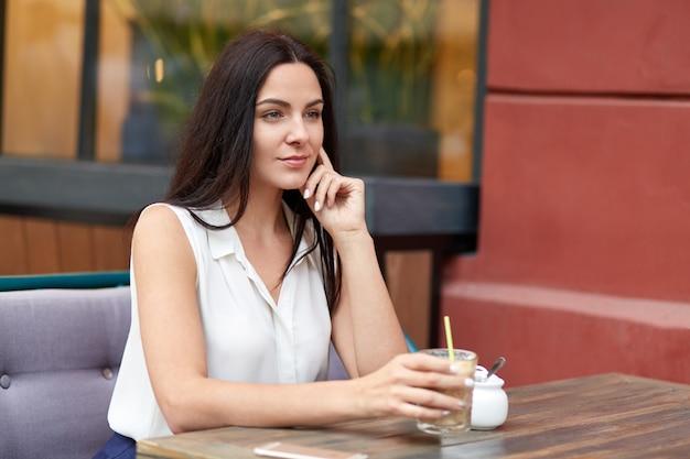 Femme pensive rêveuse aux cheveux noirs, vêtue de vêtements formels, boit un cocktail, passe du temps libre dans une cafétéria en plein air, concentrée dans la distance