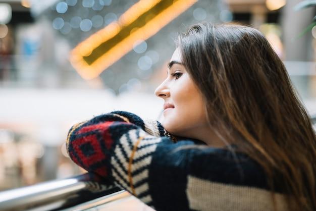 Femme pensive se penchant sur la rambarde