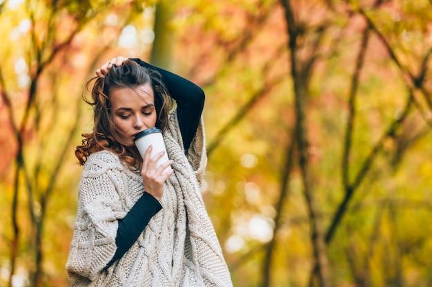 Une femme pensive se tient avec une tasse de café dans le parc