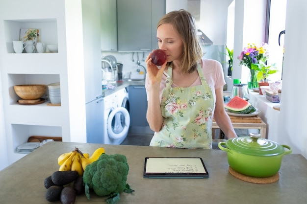 Femme pensive, sentir les fruits pendant la cuisson dans sa cuisine, à l'aide de tablette près de casserole et de légumes frais sur le comptoir. vue de face. cuisiner à la maison et concept d'alimentation saine