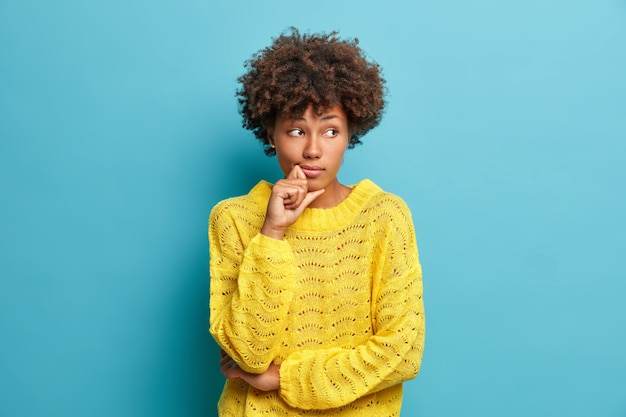 Femme pensive sérieuse avec des cheveux afro regarde ailleurs et se tient dans une pose réfléchie pense aux problèmes et aux difficultés vêtus d'un pull jaune chaud isolé sur un mur bleu prend une décision
