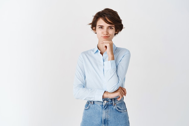 Femme pensive souriante ayant une idée, souriante rusée se sentant intéressée, debout sur un mur blanc