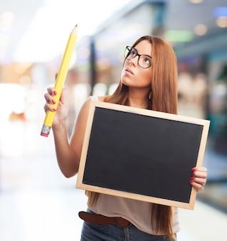 Femme pensive avec tableau noir et un crayon