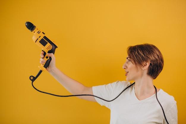Femme avec perceuse électrique sur fond jaune