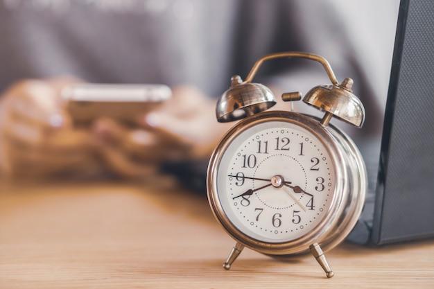 Femme perdant du temps au travail avec alarme sur le bureau