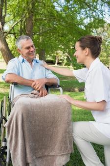 Femme avec père assis dans une chaise roulante au parc