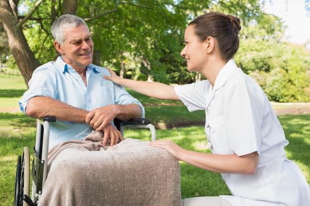 Femme avec père mûr assis dans une chaise roulante au parc
