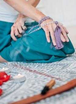 Femme avec des perles de mala lilas sur ses mains henné mehendi