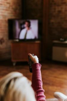 Femme permutant entre les chaînes de télévision