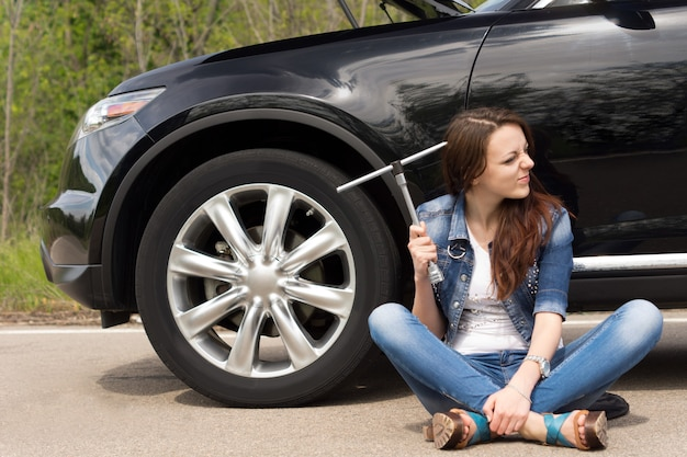 Femme perplexe en attente d'assistance routière