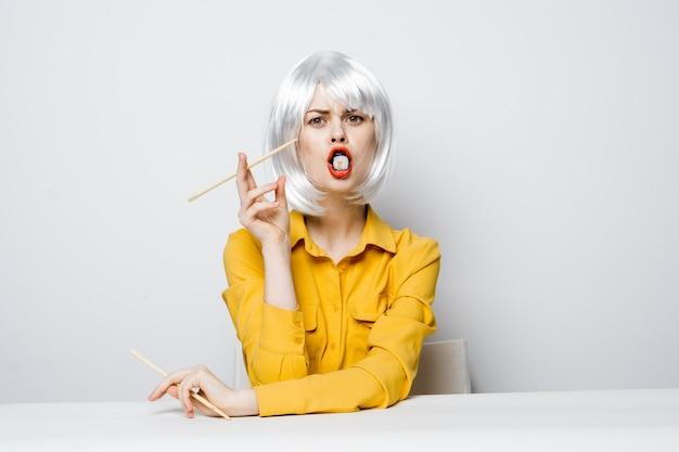 Femme en perruque blanche sushi roule baguettes de nourriture diététique