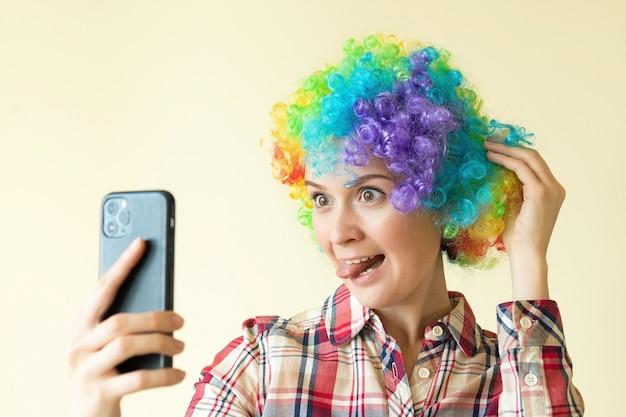 Femme en perruque de couleur clown prenant selfie, drôle de jour d'imbéciles