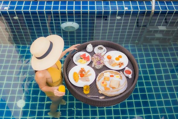 Femme avec petit déjeuner flottant autour de la piscine