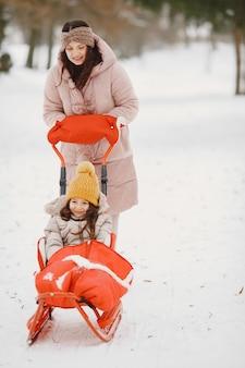 Femme et petite fille dans un parc avec traîneau