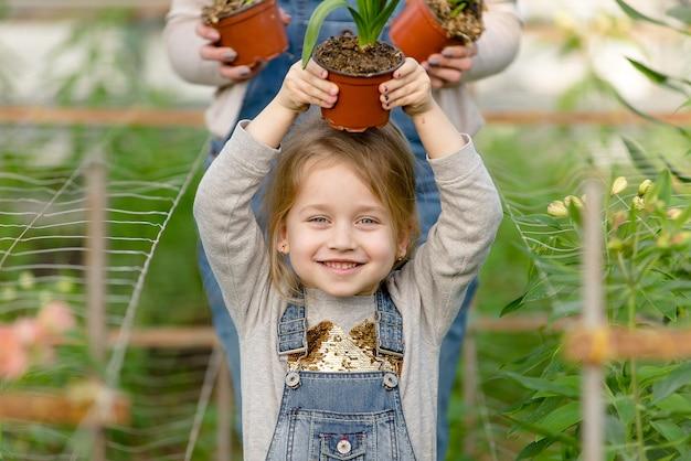Une femme avec une petite fille garde des fleurs en pot dans une serre au printemps.