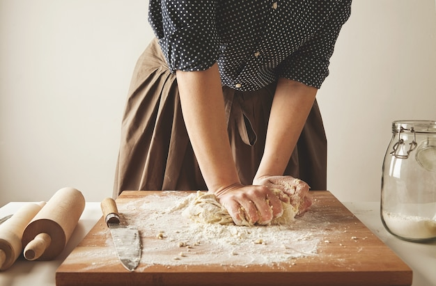 Femme pétrit la pâte pour pâtes sur planche de bois près de deux rouleaux à pâtisserie et pot de farine
