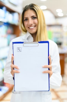 Femme pharmacien tenant un presse-papiers vierge avec le texte rx dessus