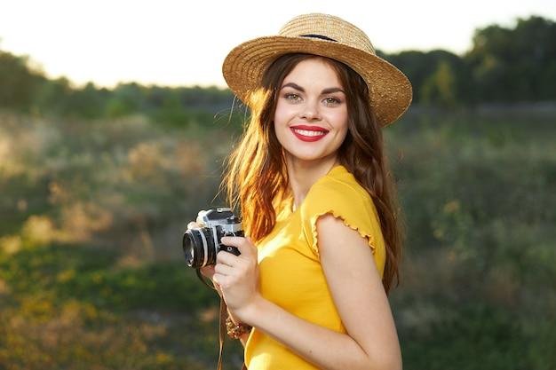 Femme photographe avec un appareil photo dans ses mains sourire lèvres rouges t-shirt jaune hat walk