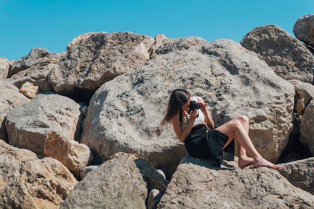 Femme photographe assis sur un rocher prenant une photo avec l'appareil photo près de la mer