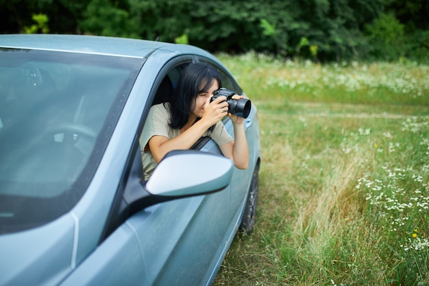 Une femme photographe assise dans la voiture et photographiant un paysage de champ de fleurs, une femme de voyage prend une photo, un espace pour le texte.
