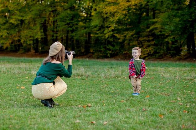 Femme photographe photographiant l'enfant à passer à l'extérieur dans le parc