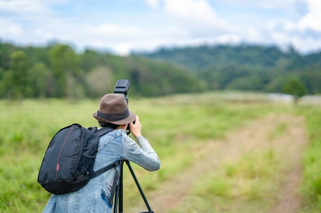 Femme photographe prend des photos sur les collines, elle tenant et en regardant la caméra.