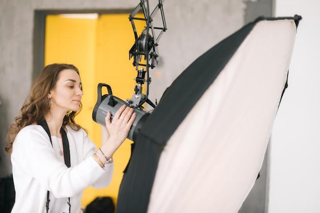 Une femme photographe prépare une boîte à lumière d'équipement léger pour une séance photo en studio