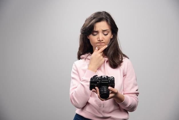 Femme photographe regardant des photos sur un mur gris.