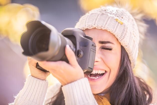 Une femme photographe souriante dans une casquette d'hiver prend une photo à l'extérieur.
