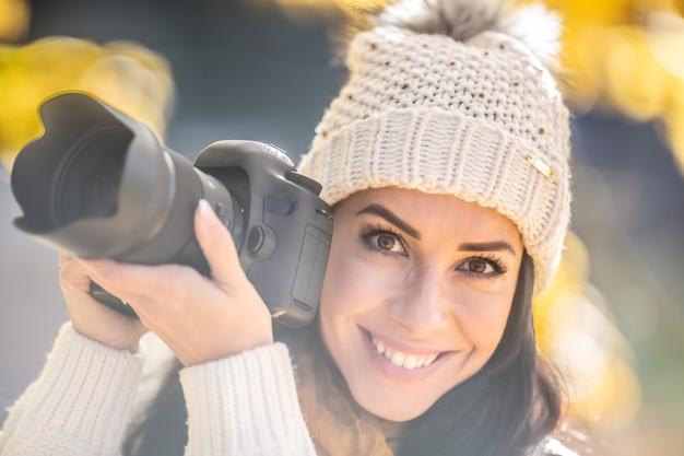 Une femme photographe souriante et séduisante dans un chapeau à pompon prend des photos à l'extérieur par une journée ensoleillée d'automne.