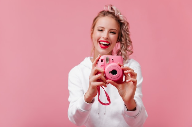 Femme photographe souriante travaillant sur un mur rose