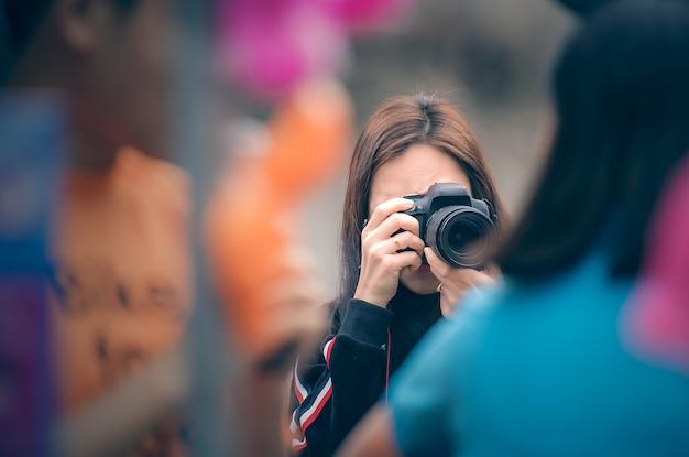 Femme photographe tenant appareil photo reflex numérique prendre des photos