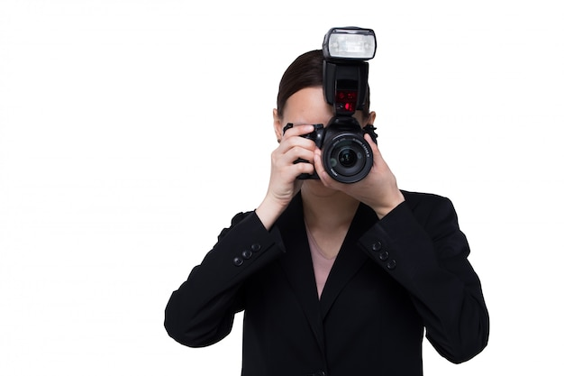 Femme photographe tenir la caméra avec un point d'éclair externe, fond blanc isolé
