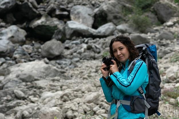 Une femme photographie le paysage dans les montagnes.