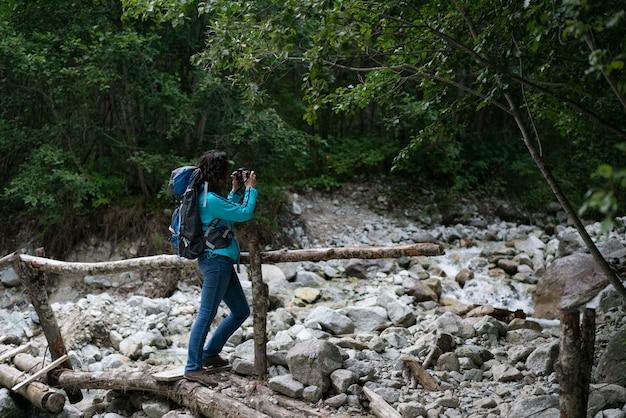 Une femme photographie une rivière dans les montagnes du caucase du nord.